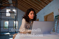 Picture of a hispanic woman architect working on her laptop at a new construction site with unfinish construction work in the background